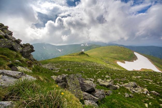 Szeroka panorama oświetlonego słońcem górskiego płaskowyżu z zieloną trawą, płatami śniegu i dużymi głazami na odległych górach pod sceną pochmurnego nieba. piękno przyrody, turystyki i koncepcji podróży.