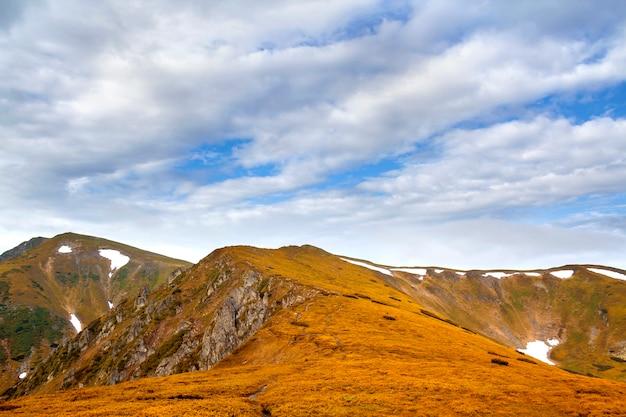 Szeroka panorama oświetlonego słońcem żółtego grzbietu gór skalistych z płatami śniegu w dolinach rozciągających się po horyzont pod jasnym niebieskim tle pochmurnego nieba. piękno przyrody, turystyki i koncepcji podróży.