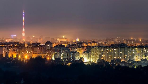 Szeroka panorama, widok z lotu ptaka w nocy nowoczesne miasto iwano-frankowsk, ukraina. scena jasnych świateł wysokich budynków, wysokiej wieży telewizyjnej i zielonych przedmieść.