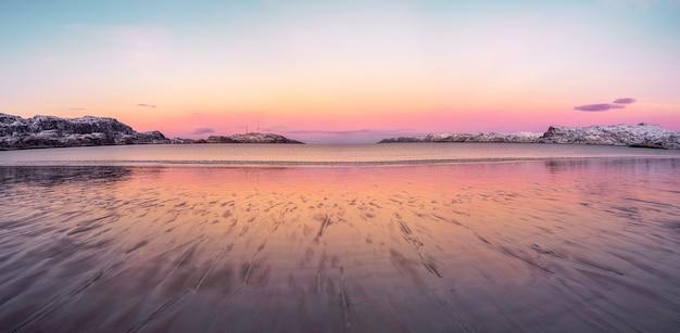 Szeroka panorama zimowego zachodu słońca w niesamowitym kolorze magenty nad fiordem. teriberka, rosja.