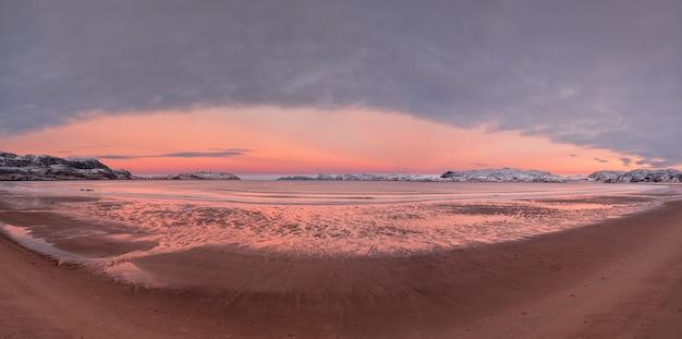 Szeroka panorama zimowego zachodu słońca w niesamowitym kolorze magenty nad fiordem.