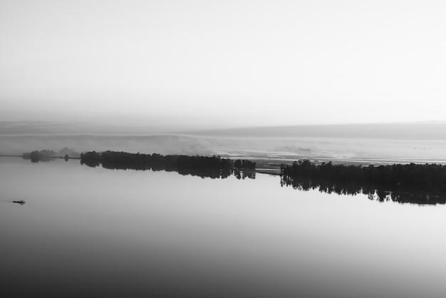 Szeroka rzeka płynie wzdłuż ukośnego brzegu z sylwetką lasu i gęstą mgłą w skali szarości