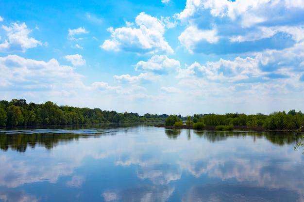 Szeroka rzeka z zielonymi brzegami i odbijającym się niebem z chmurami. sceneria