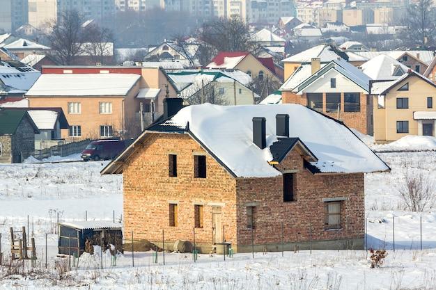 Szeroka zimowa panorama terenów wiejskich pod zabudowę w cichym podmiejskim obszarze mieszkalnym. nowy, nieukończony murowany dom odległej wioski i wysokich budynków miasta pod błękitnym niebem.