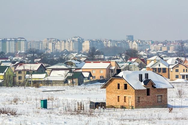 Szeroka zimowa panorama terenów wiejskich pod zabudowę w cichym podmiejskim obszarze mieszkalnym.