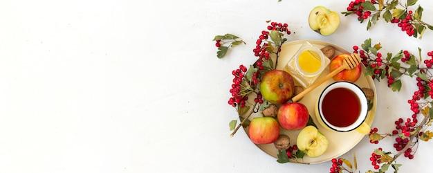 Szeroki baner z miejsca kopiowania tekstu. przytulna jesienna, gorąca, przyprawiona herbata z miodem, jabłkami i czerwonymi jagodami głogu na tacy. martwa natura na białym tle. leżał płasko.