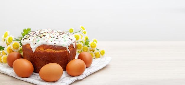 Szeroki baner z wielkanocnym tortem i barwionymi jajkami żółty kwiat kwitnie na tle