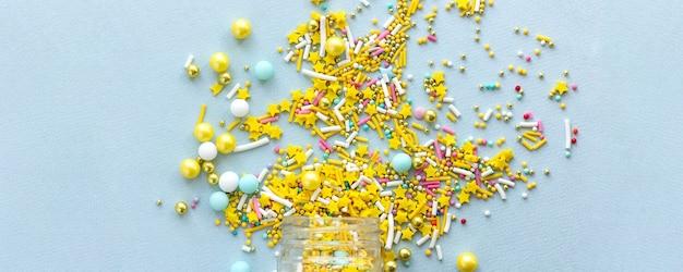 Szeroki baner żółty cukier kropi ziarnisty na niebieskim tle, leżał z bliska płasko.