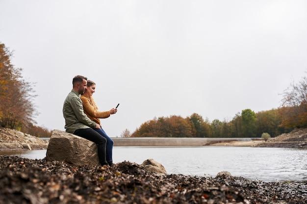 Szeroki kąt para siedzi nad jeziorem, patrząc na telefon komórkowy na zewnątrz z jeziorem