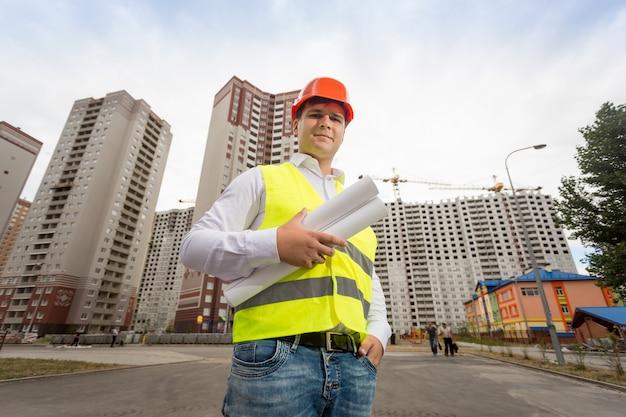 Szeroki kąt portret inżyniera budowlanego w kasku pozującym przed właśnie zbudowanymi budynkami