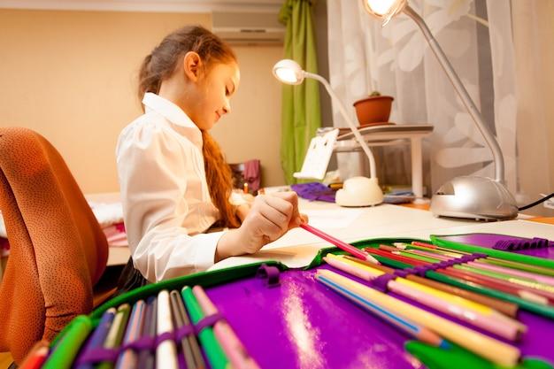 Szeroki kąt portret małej dziewczynki biorącej ołówek z piórnika of