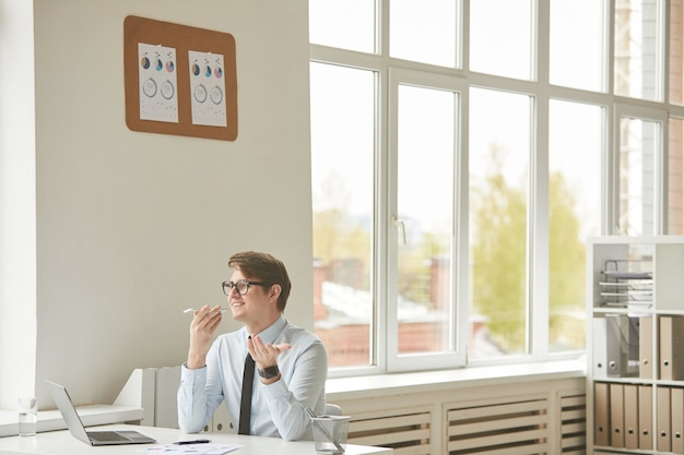 Szeroki kąt portret wesoły młody biznesmen nagrywający wiadomość głosową za pomocą smartfona, siedząc przy biurku w białym wnętrzu biurowym, miejsce na kopię