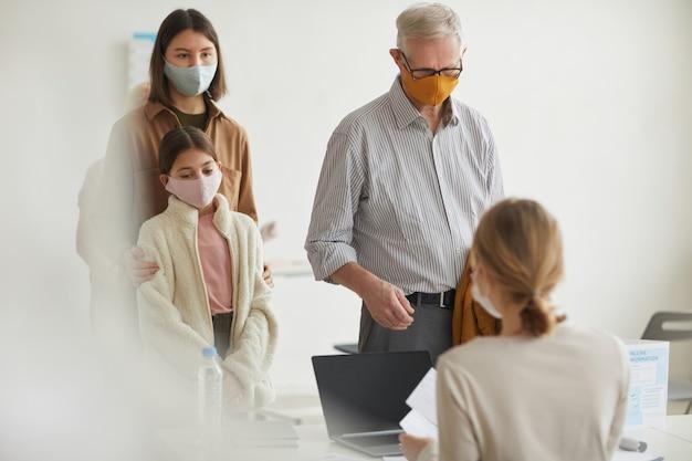 Szeroki kąt portret współczesnego starszego mężczyzny rejestrującego się na szczepionkę przeciw covid w klinice medycznej, kopia przestrzeń
