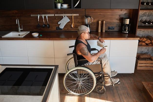 Szeroki kąt portret współczesnej wytatuowanej kobiety na wózku inwalidzkim, robiącej kawę w domu, kopia przestrzeń
