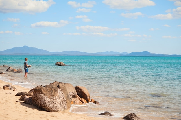 Szeroki kąt strzału człowieka połowów na plaży pod jasnym, błękitnym niebem