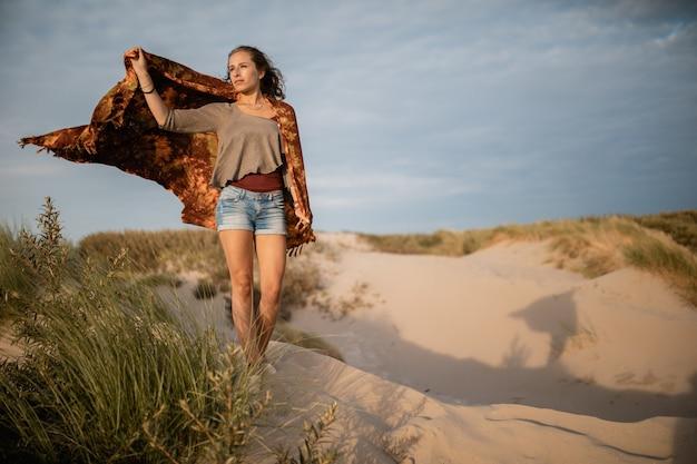 Szeroki kąt strzału kobiety idącej po piasku w ciągu dnia