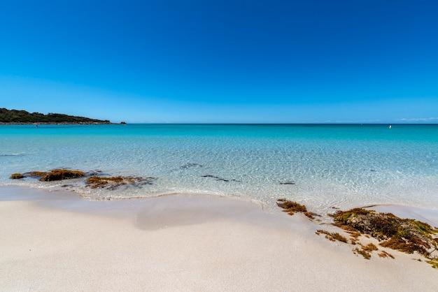 Szeroki kąt strzału niektórych skał na plaży green bay w australii zachodniej pod błękitnym niebem