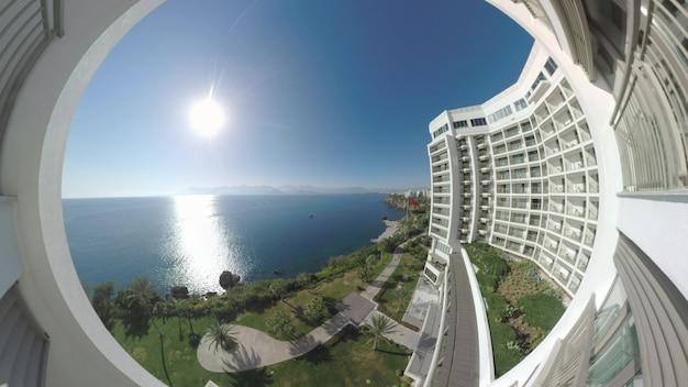 Szeroki kąt strzału z widokiem hotelu na brzeg morza śródziemnego. scena z zielonym nabrzeżem i jasnym słońcem świecącym i odbijającym się w wodzie. wakacje w antalyi w turcji