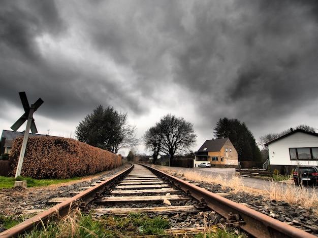 Szeroki kąt ujęcia torów kolejowych otoczonych drzewami pod zachmurzonym niebem