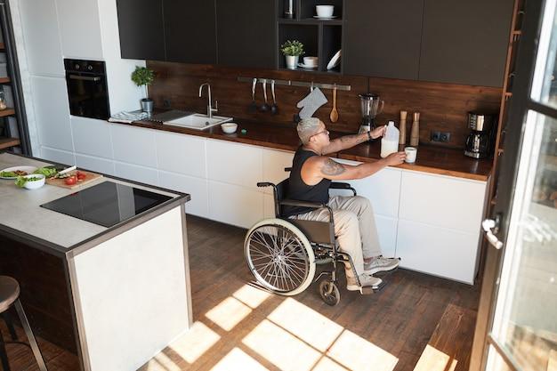 Szeroki kąt ujęcia współczesnej wytatuowanej kobiety na wózku inwalidzkim, która robi kawę w domu oświetloną światłem słonecznym, kopia przestrzeń