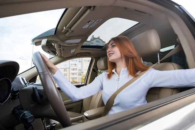 Szeroki kąt widzenia młodego rudowłosego kierowcy zapinanego za pomocą pasa bezpieczeństwa prowadzącego samochód z uśmiechem.