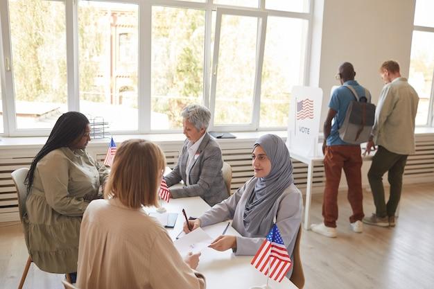 Szeroki kąt widzenia osób głosujących w lokalu wyborczym w dniu wyborów, miejsce na kopię