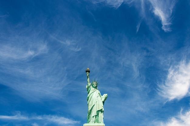 Szeroki kąt widzenia statuy wolności na zachmurzone błękitne niebo, nowy jork.
