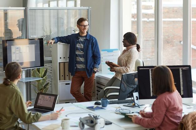 Szeroki kąt widzenia wieloetnicznego zespołu programistów it omawiającego projekt podczas spotkania w biurze, kopia przestrzeń