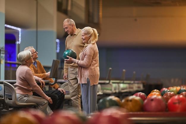 Szeroki kąt widzenia z boku na grupę starszych osób grających razem w kręgle, jednocześnie ciesząc się aktywną rozrywką w kręgielni, kopia przestrzeń