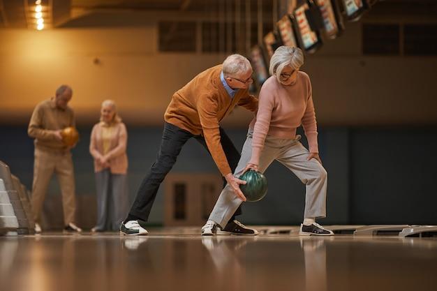 Szeroki kąt widzenia z boku na nowoczesnej starszej parze grającej razem w kręgle, ciesząc się aktywną rozrywką w kręgielni, kopia przestrzeń