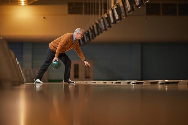 Szeroki kąt widzenia z boku na starszego mężczyznę grającego w kręgle samotnie, ciesząc się aktywną rozrywką w kręgielni, kopiuj przestrzeń