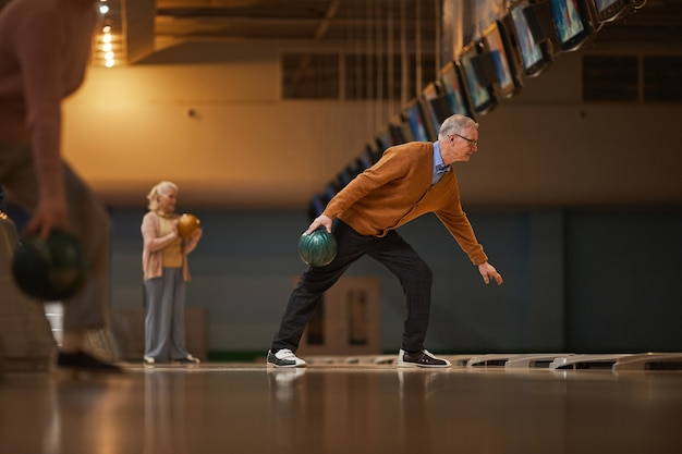 Szeroki kąt widzenia z boku na starszych ludzi grających w kręgle podczas aktywnej rozrywki w kręgielni, kopia przestrzeń