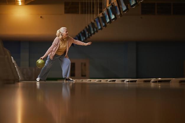 Szeroki kąt widzenia z boku starszej kobiety grającej w kręgle samotnie, ciesząc się aktywną rozrywką w kręgielni, kopia przestrzeń