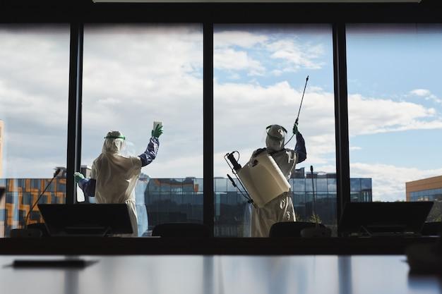Szeroki kąt widzenia z tyłu portret dwóch pracowników w kombinezonach hazmat dezynfekujących okna w biurowcu stojącym na tle błękitnego nieba,