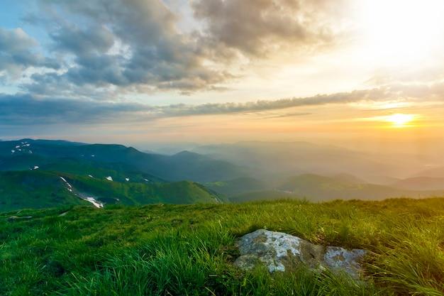 Szeroki lato widok na góry o wschodzie słońca. świecące pomarańczowe słońce wznoszące się w błękitne pochmurne niebo nad zielonym trawiastym wzgórzem z dużą skałą i odległym pasmem górskim porannym mgłą. pojęcie piękna przyrody.