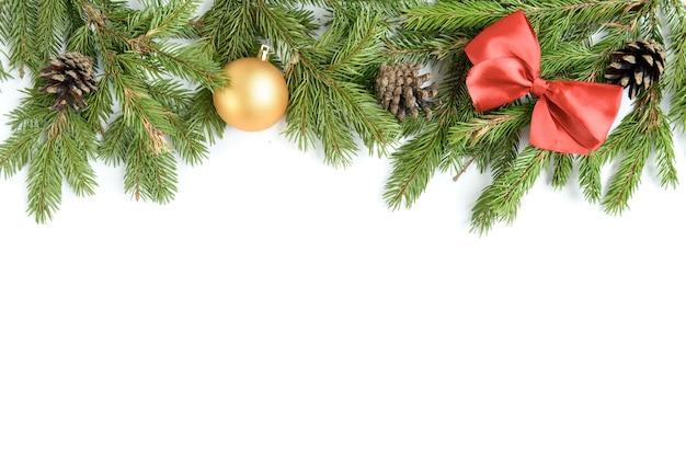 Szeroki łuk w kształcie świątecznej granicy na białym tle, złożony ze świeżych gałęzi jodły, szyszek i kokardki