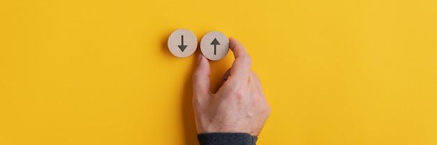 Szeroki obraz męskiej dłoni umieszczającej dwa drewniane wycięte kółka ze strzałkami skierowanymi w górę iw dół na żółto.