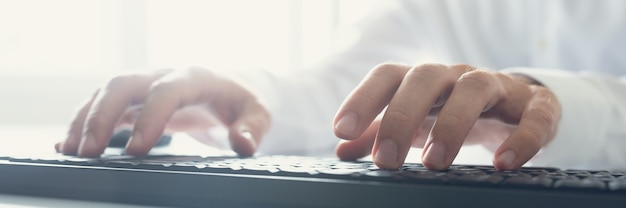 Szeroki obraz programisty piszącego za pomocą czarnej klawiatury z rozbłyskiem słonecznym dochodzącym z okna biura.