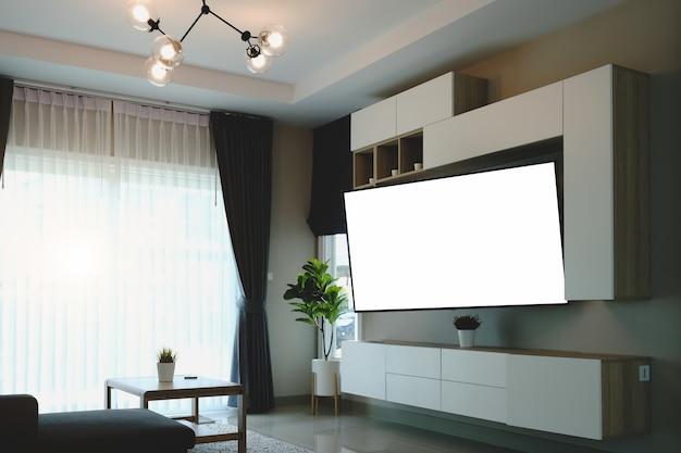 Szeroki pusty telewizor na białym stojaku w pobliżu lekkiej ściany w salonie.