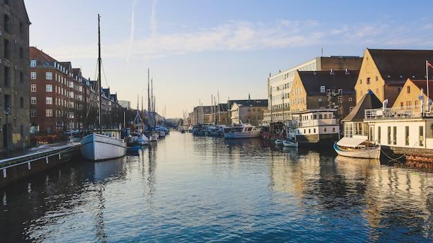 Szeroki strzał łodzie na ciele wody blisko budynków w christianshavn, kopenhaga, dani