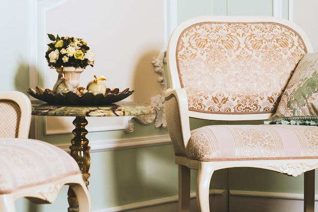 Szeroki strzał zbliżenie bukiet kwiatów w wazonie na stole w pobliżu eleganckiego fotela