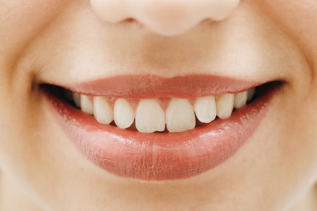Szeroki uśmiech młodej, świeżej kobiety z wielkimi, zdrowymi, białymi zębami.