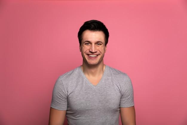 Szeroki uśmiech. wesoły młody człowiek w szarej koszulce, który patrzy w kamerę i uśmiecha się radośnie.