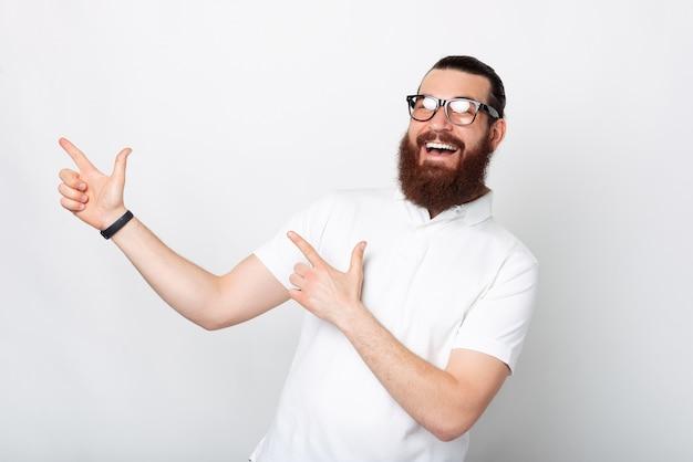 Szeroki uśmiechnięty brodaty mężczyzna wskazuje na bok na wolne miejsce.