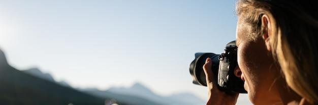 Szeroki widok obrazu młodej kobiety fotograf robienia zdjęć gór w oddali.