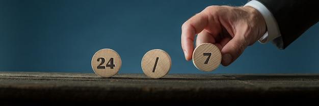 Szeroki widok obrazu ręki biznesmena montującego znak 24/7 z drewnianymi wyciętymi kółkami.