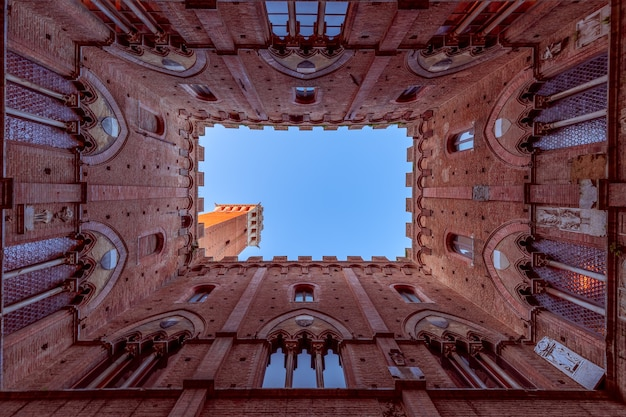Szeroki widok z dziedzińca palazzo pubblico na słynną torre del mangia. siena, toskania, włochy