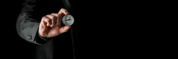 Szeroki widok z przodu dłoni pokazującej kompas do aparatu, z mężczyzną incognito w apartamencie w nieostrości