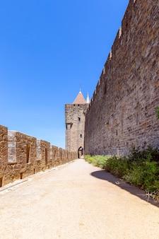 Szerokie mury obronne z chodnikami i łukami średniowiecznego zamku miasta carcassonne