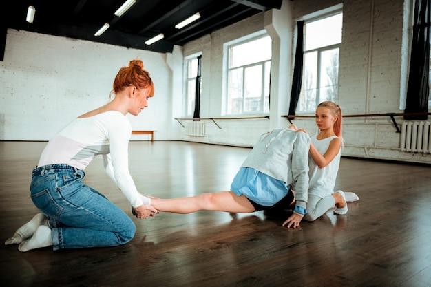 Szerokie nogi. ciemnowłosa nastolatka z pokolenia z w sportowym stroju robi rozcięte nogi pod okiem nauczyciela